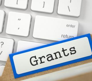 Grants typed out on a label next to a keyboard.