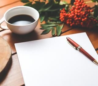 Photo of a black piece of paper, a pen, and a cup of coffee.
