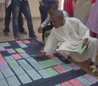 program participants placing tasks into a logics model laid out on the floor