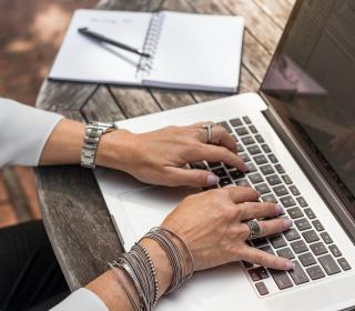 hands typing on computer with notebook nearby